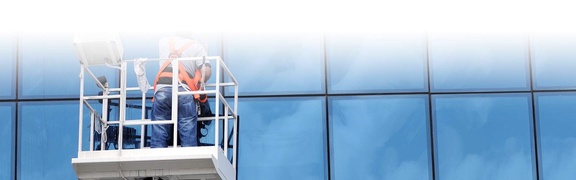 Mann auf Hebebühne macht Fassadenreinigung